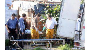 Ingrato trabajo. Bomberos y policías tuvieron que sacar del pozo los 14 pedazos del cuerpo de la jovencita.
