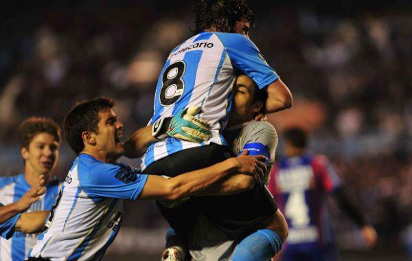 El arquero Saja festeja con sus compañeros el gol que metió de penal. (Foto: Télam)