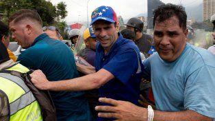 Gaseado. Henrique Capriles (c.) sufre los efectos del gas pimienta.