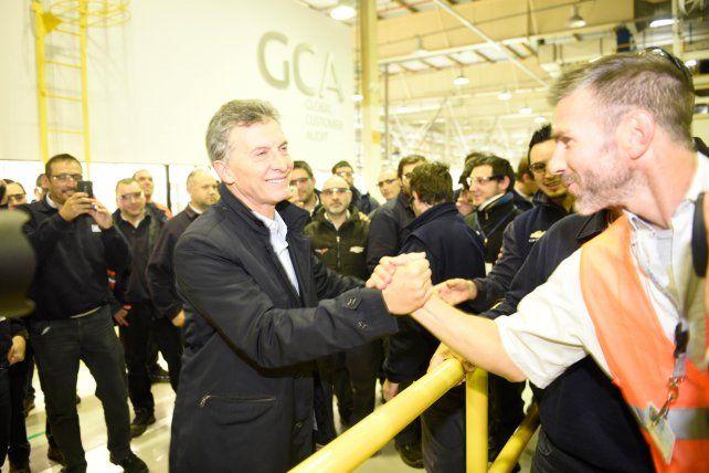 Mano a mano. El presidente Macri saluda a un trabajador de GM durante la recorrida que hizo el miércoles por la planta.