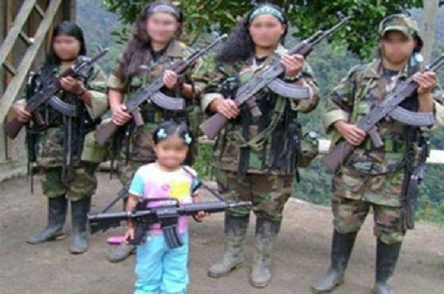 Niñas soldado de las Farc se exhiben junto a una pequeña en un campamento en las selvas colombianas.