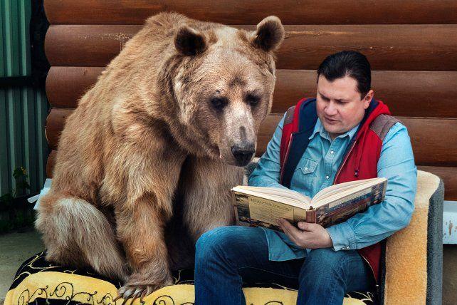 El oso Stepan comparte una lectura junto a su padre adoptivo Yuriy.