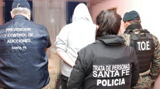 Uno de los diez detenidos es trasladado por personal policial santafesino tras uno de los allanamientos.