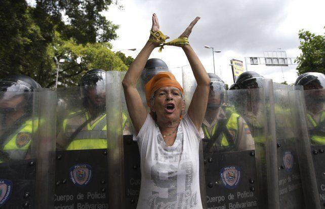 Protestas. Una mujer desafía el hermético cordón policial en Caracas.