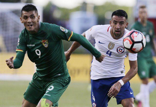 El boliviano Yasmani Duk y el chileno Mauricio Isla pelean por la pelota.