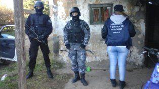 Efectivos policiales custodian uno de los domicilios allanados esta mañana.