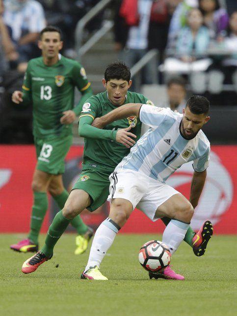 Es mía. El Kun Agüero aguanta la pelota ante el acoso del boliviano Azogue.