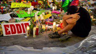 Homenajes. Un joven permanece sentado ante el memorial a las víctimas de la masacre en Orlando.