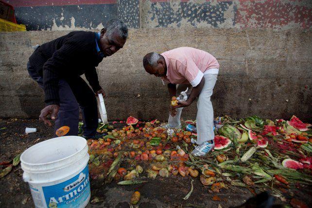 hambre. Dos vecinos de Caracas buscan comida en un basural. La grave situación no deja de empeorar.