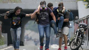 Represión. Manifestantes retiran a un herido en medio de gases lacrimógenos en una protesta en Caracas.