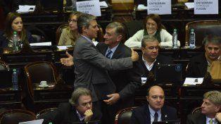 Los diputados Binner y Grandinetti se cruzan en un cálido saludo durante la sesión.