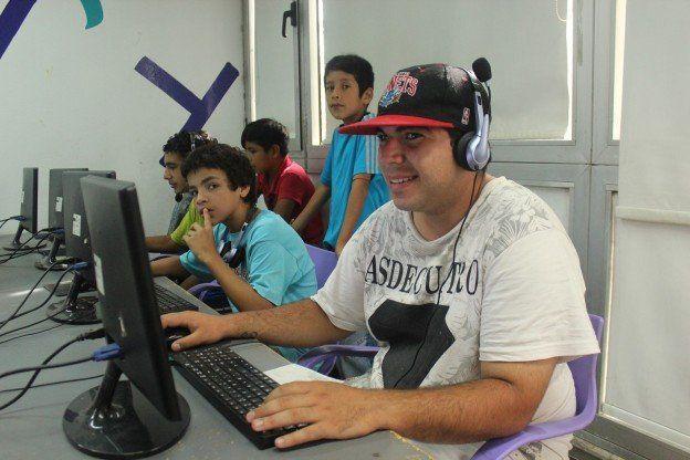 a full. Los chicos utilizan computadoras y teléfonos celulares para producciones de contenidos y juegos.
