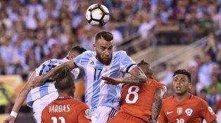 Otamendi se eleva para cabecear entre dos jugadores chilenos.