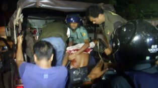 Efectivos policiales y de las fuerzas de salud atienden a los heridos en el atentado en Bangladesh.