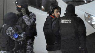 Con casco. Rodeado de guardias camuflados y con chaleco antibalas