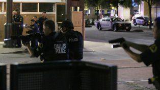 Efectivos de la Policía de Dallas se atrinchera detrás de un móvil durante los enfrentamientos.