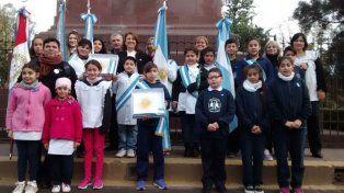 La intendenta en el Monumento a Belgrano del Parque Independencia junto a los chicos abanderados.