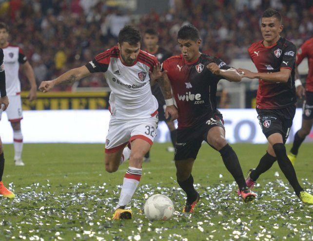 La pelea. Nacho Scocco intenta maniobrar ante la marca mexicana. Newells fue superado por Atlas en Guadalajara.