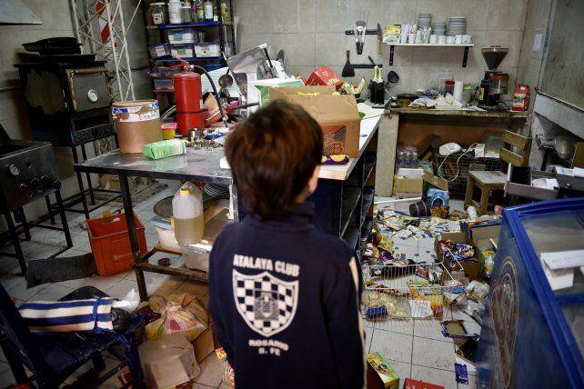 Un niño con la indumentaria del club observa desconsolado los destrozos en las isntalaciones de Atalaya.