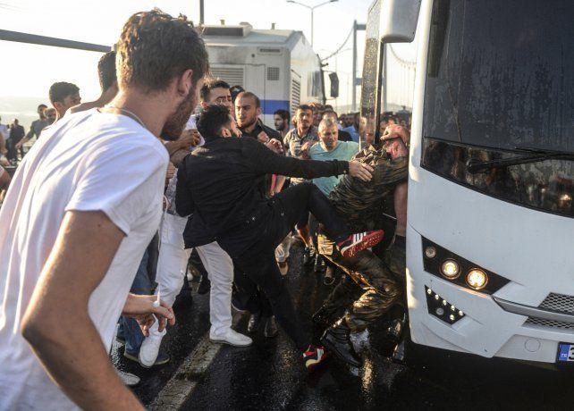 Bronca y Represalias. Un civil turco patea a un soldado arrestado por participar de la asonada golpista.