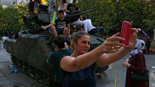Souvenir. Una vecina se saca una selfie ante un blindado de infantería abandonado por los golpistas.