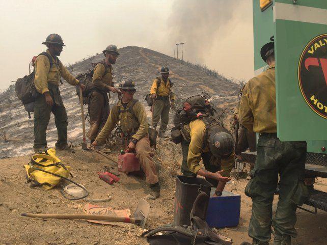 Sin tregua. Un grupo de bomberos se reponen del intenso trabajo.