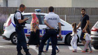 Convivencia. Una familia de inmigrantes musulmanes pasa frente a dos oficiales en la localidad normanda.