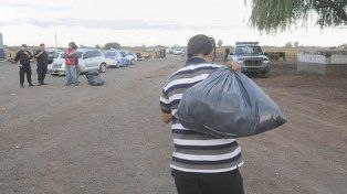 misterio. Un policía de civil se lleva una bolsa de la chacra. Los dueños del lugar dijeron que tenía mucho dinero.