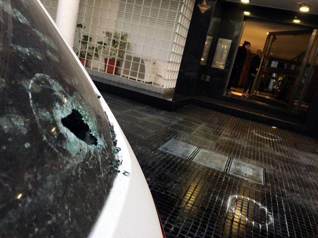 El vidrio impactado y las marcas de las balas en el piso
