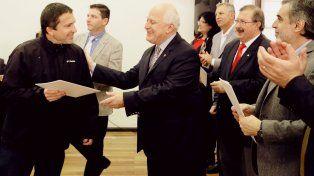 Lifschitz entrega a uno de los beneficiarios el acta que oficializa su pase a la planta permanente provincial.