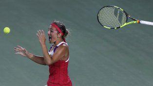 La portorriqueña Mónica Puig lanza la pelota y su raqueta al aire tras ganar el oro olímpico ante la alemana Angelique Kerber.