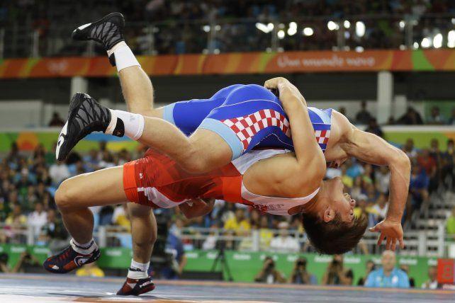 El surcoreano Hyeon-woo Kim (de malla roja) y el croata Bozo Starcevic en la pelea por el bronce de la lucha grecorromana en 75 kilogramos.