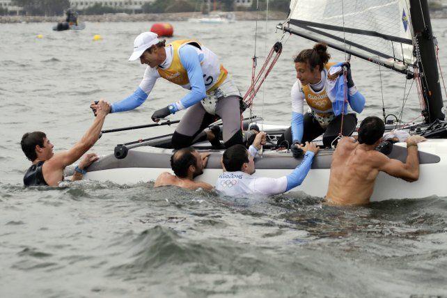Santiago Lange y Cecilia Carranza reciben saludos desde el agua segundos después de haberse adjudicado la medalla dorada en la especialidad Nacra 17 mixta.