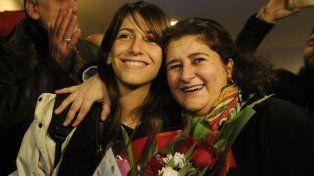 Muy felices. La joven Hannen Assad (izquierda) es recibida con un ramo de flores en Ezeiza por uno de los familiares que le da refugio en La Pampa.