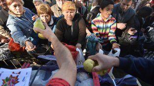 De a tres. Muchísima gente se acercó a recibir peras y manzanas gratis.