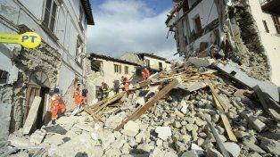 Los rescatistas llevan en camilla a una de las víctimas a través de un edificio en ruinas enArquata del Tronto.