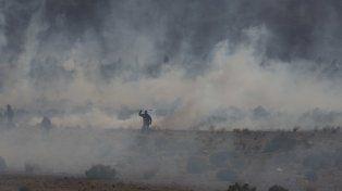 Mineros emergen de una nube de gases lacrimógenos.