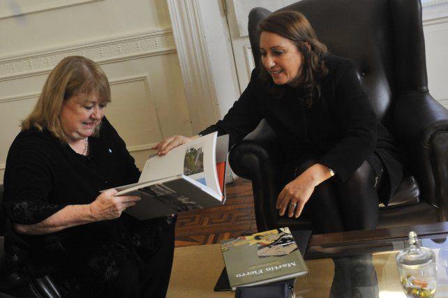 Malcorra recibe un libro de parte de la intendenta Fein durante la reunión de esta mañana en el Palacio de los Leones.