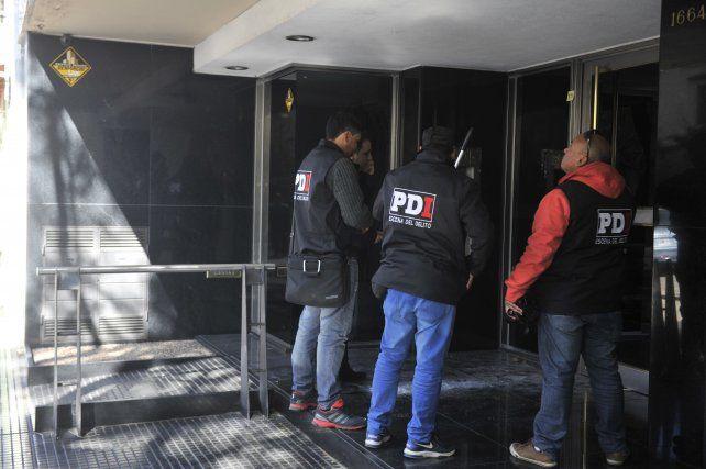 La policía pericia uno de los edificios que recibió impactos de bala.
