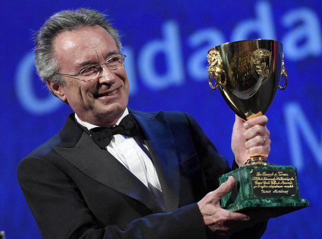 Premiado. El actor sobre el escenario del Palazzo del Cinema y sosteniendo la Copa Volpi que consagra a los grandes.