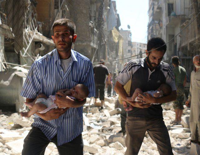Desolador. Civiles rescatan a dos bebes entre las ruinas de un bombardeo en Alepo. Ocurrió el domingo.