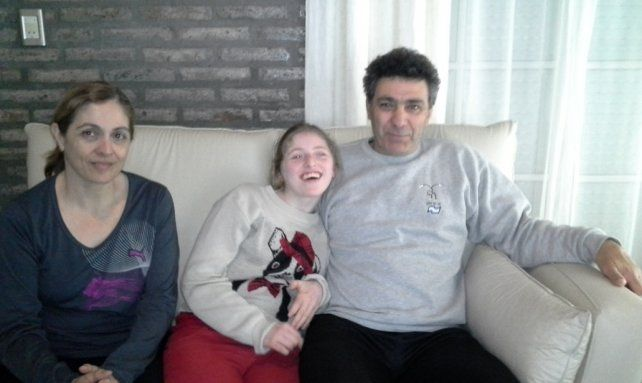 En familia. Martina y sus padres. Ella padece un trastorno neurológico y consume el aceite para las convulsiones.