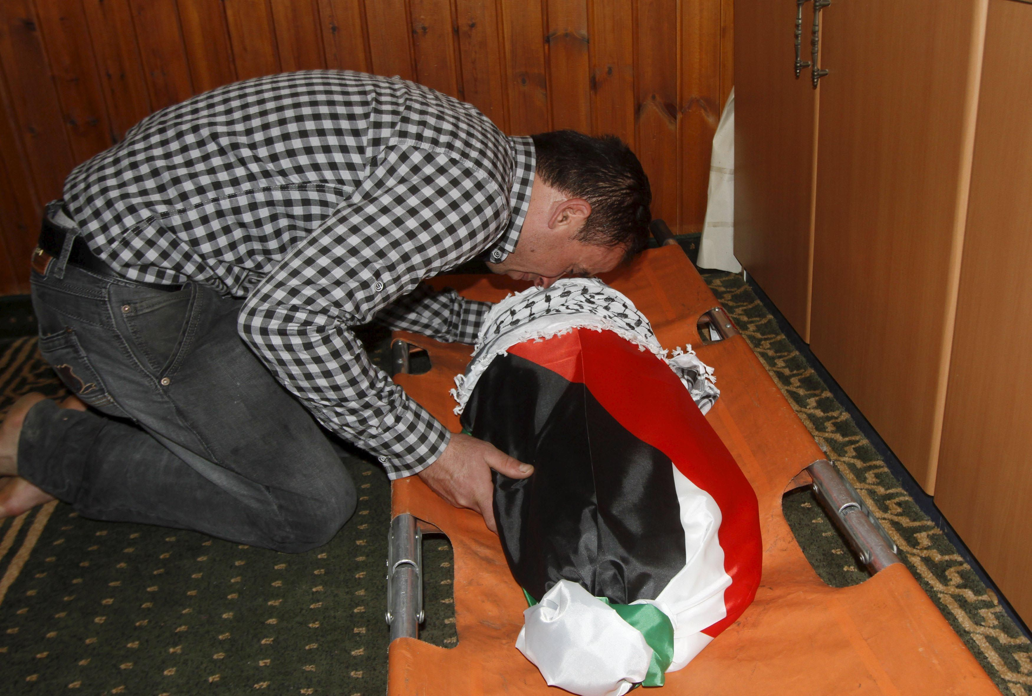 Horror. Un pariente de la familia palestina atacada junto al pequeño cuerpo sin vida del bebé que murió quemado.