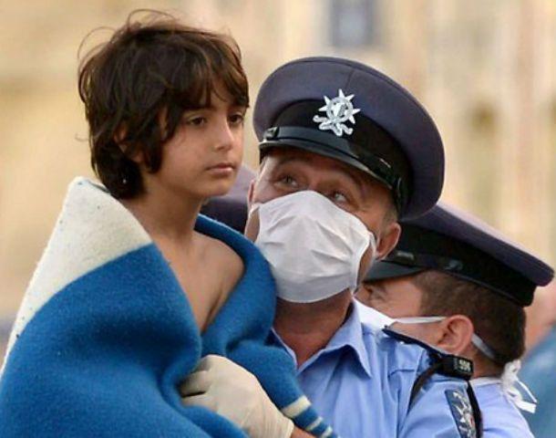 Miradas. Un chico rescatado de una de las barcazas que naufragó no sabe qué le espera. Al guardia lo reconforta haberlo salvado.