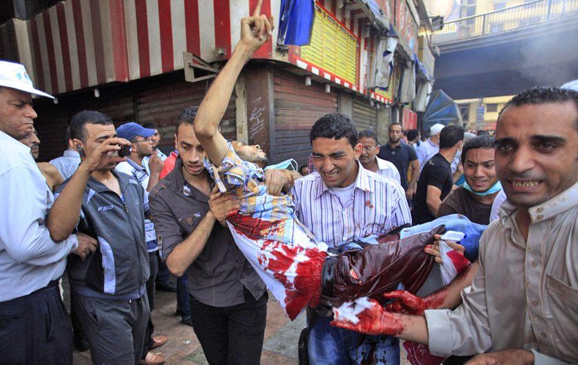 Caos verdadero. Una persona herida en los habituales enfrentamientos en las calles de El Cairo es auxiliada.