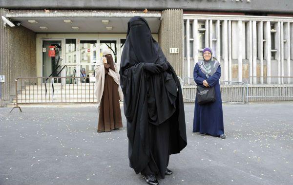 Dos mujeres con velos integrales (con burka en primer plano y Niqab a la izquierda). La tercera