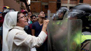 Clamor En las calles. Una monja reclama a la policía caraqueña que desbloquee el paso a los manifestantes.