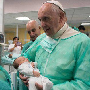 Consuelo. Francisco sostiene a un bebé en el Hospital San Giovanni.