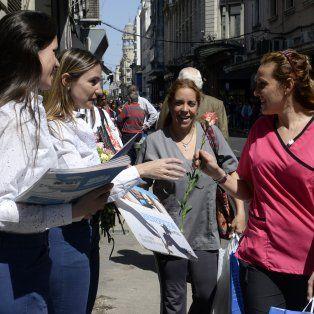 Promotoras de La Capital entregaron flores y una gúia de beneficios a los transeúntes por el día de la Primavera.