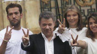 Santos y su familia hacen el símbolo de la paz luego de votar en el plebiscito.